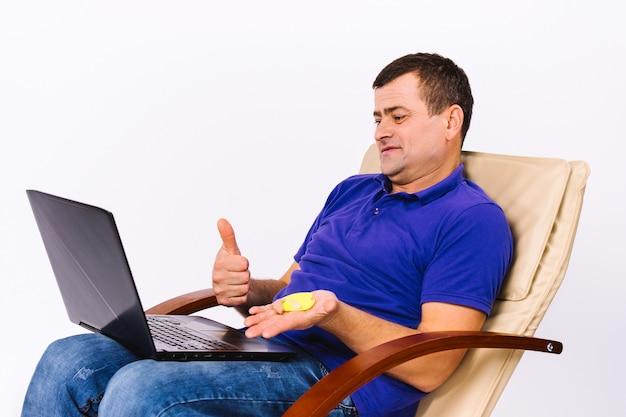 Starszy głuchy mężczyzna trzyma aparat słuchowy w ręku i pokazuje kciuk w górę na aparat laptopa, podczas gdy