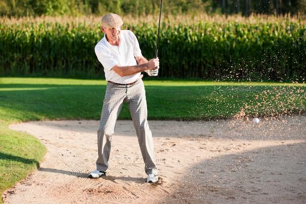 Starszy golfista w pułapce piasku