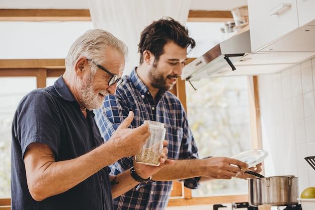 Starszy gotowania w kuchni z synem, happy family man moment dobry mentor opieki stary człowiek od syna.
