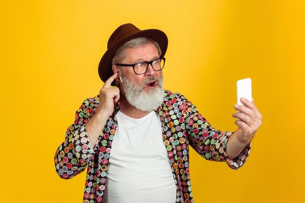 Starszy hipster mężczyzna noszący okulary pozowanie na żółtym tle