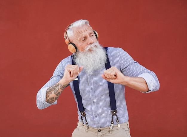 Starszy hipster mężczyzna tańczy na świeżym powietrzu podczas słuchania muzyki z bezprzewodowymi słuchawkami z czerwonym tłem