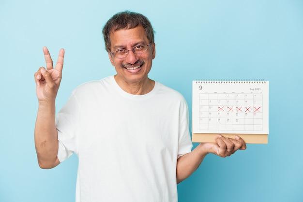 Starszy indianin trzyma kalendarz na białym tle na niebieskim tle radosny i beztroski pokazujący palcami symbol pokoju.