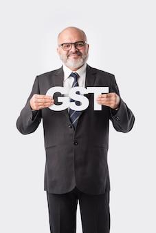Starszy indyjski azjatycki biznesmen trzyma coś lub afisz. edytowalna fotografia koncepcyjna