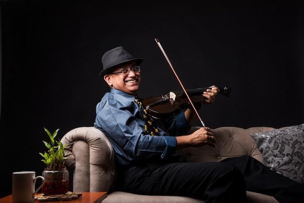 Starszy indyjski azjatycki przystojny mężczyzna grający lub pozujący z muzycznym instrumentem smyczkowym, takim jak gitara lub skrzypce, stojąc na czarnym tle lub siedząc na kanapie lub kanapie