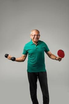 Starszy indyjski azjatycki zdrowy sportowiec grający w indywidualny sport lub gimnastykę, odizolowany na prostym tle