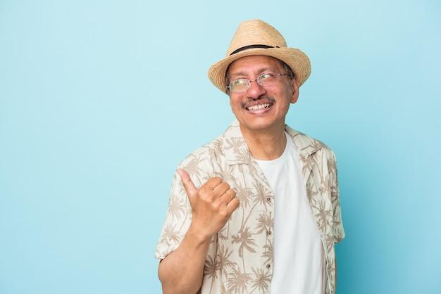 Starszy indyjski mężczyzna nosi ubrania letnie samodzielnie na niebieskim tle starszy indyjski kobieta nosi strój afrykański samodzielnie na białym tle punktów z palcem kciuka, śmiejąc się i beztroski.