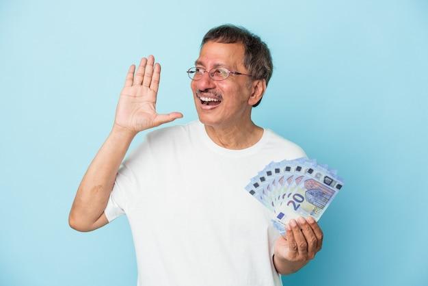 Starszy indyjski mężczyzna trzyma rachunek na białym tle na niebieskim tle krzycząc i trzymając dłoń w pobliżu otwartych ust.