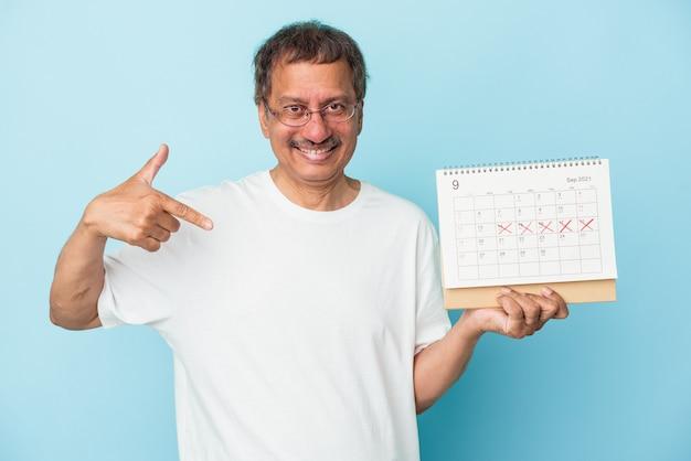 Starszy indyjski mężczyzna trzymający kalendarz na białym tle na niebieskim tle osoba wskazująca ręcznie na miejsce na koszulkę, dumna i pewna siebie