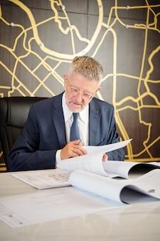 Starszy inwestor siedzący przy biurku i sprawdzający dokumenty projektu budowlanego przed podpisaniem umowy