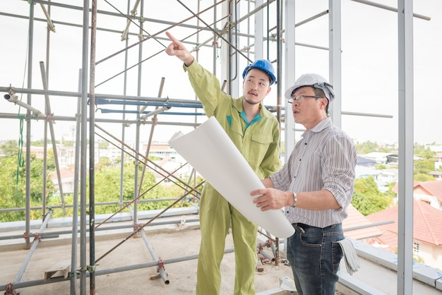Starszy inżynier budowlany kontroluje pracownika przy budową.