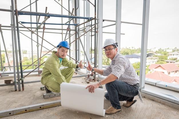 Starszy inżynier budowlany kontroluje pracownika przy placem budowy.