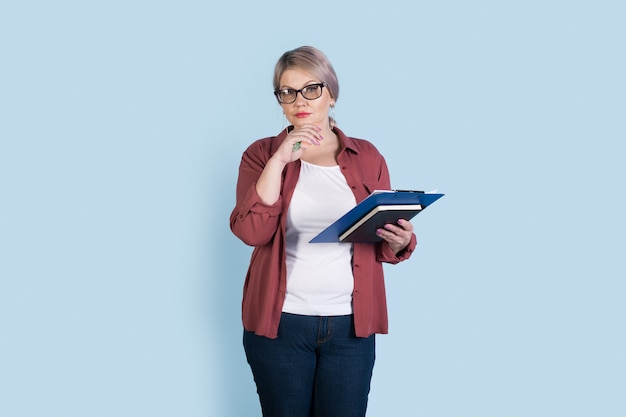 Starszy kaukaski bizneswoman pozuje na ścianie niebieskiego studia, trzymając niektóre foldery i patrząc na kamery w okularach