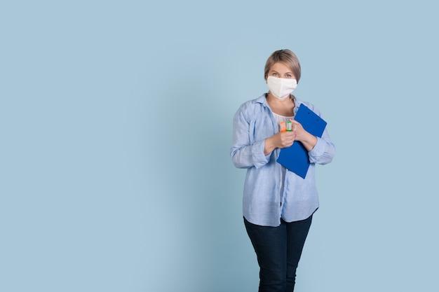 Starszy kaukaski bizneswoman z maską medyczną na twarzy, trzymając folder i markery pozuje na niebieskiej ścianie studia z wolną przestrzenią