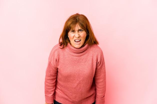 Starszy kaukaski kobieta na białym tle krzycząc bardzo zły, pojęcie wściekłości, sfrustrowany.