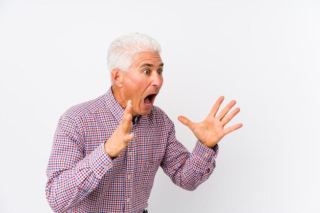 Starszy kaukaski mężczyzna na białym tle krzyczy głośno, trzyma oczy otwarte i ręce napięte.