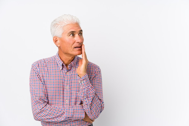Starszy kaukaski mężczyzna na białym tle mówi tajne wiadomości o gorącym hamowaniu i patrząc na bok