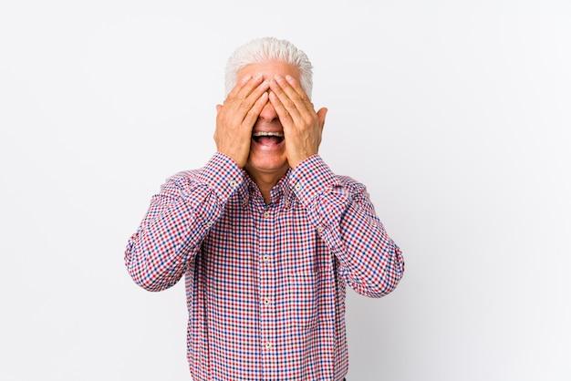 Starszy kaukaski mężczyzna na białym tle zakrywa oczy dłońmi, uśmiecha się szeroko czekając na niespodziankę.