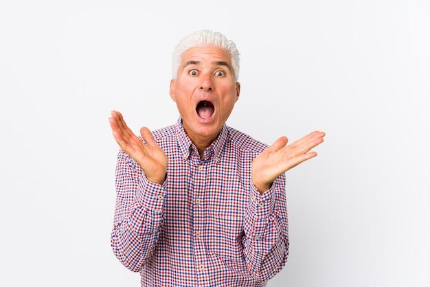 Starszy kaukaski mężczyzna na białym tle zaskoczony i zszokowany