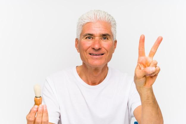 Starszy kaukaski mężczyzna ogolił się ostatnio, pokazując palcami numer dwa.