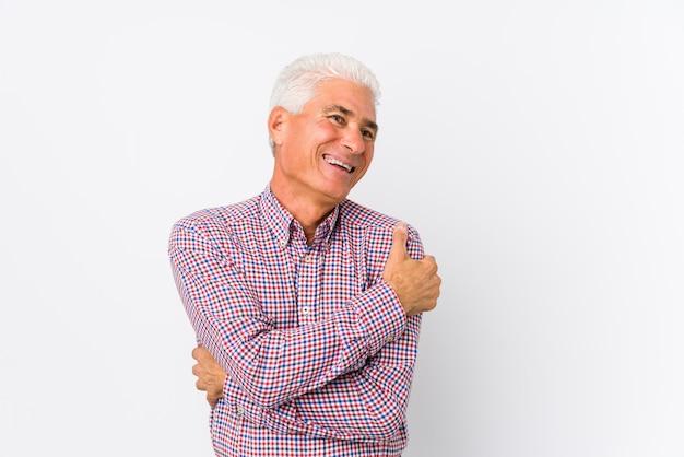 Starszy kaukaski mężczyzna przytula, uśmiechając się beztroski i szczęśliwy.