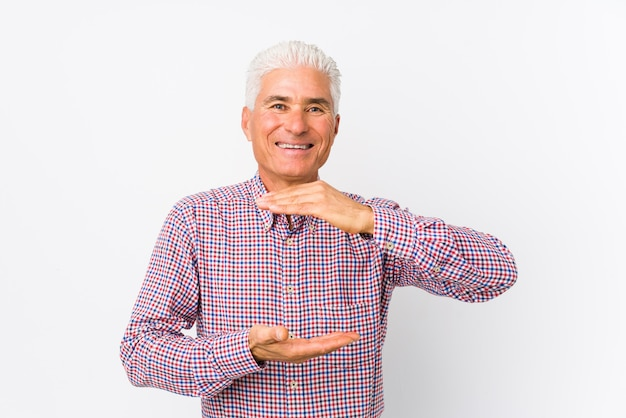 Starszy kaukaski mężczyzna trzyma coś z obu rąk