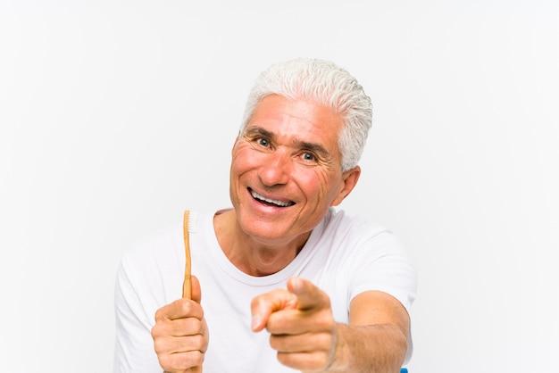 Starszy kaukaski mężczyzna trzyma szczoteczkę do zębów na białym tle wesoły uśmiechy wskazując na przód.