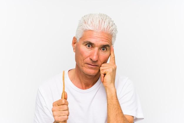 Starszy kaukaski mężczyzna trzyma szczoteczkę do zębów na białym tle, wskazując palcem na świątynię, myśląc, koncentruje się na zadaniu.