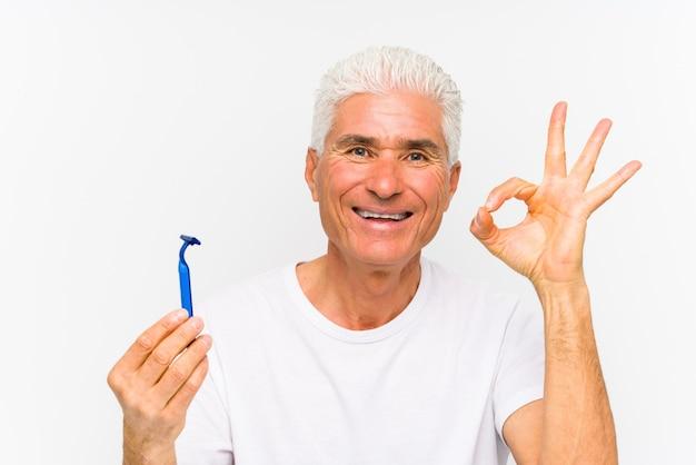 Starszy kaukaski mężczyzna trzyma żyletkę na białym tle? wesoły i pewny siebie, pokazując gest ok.