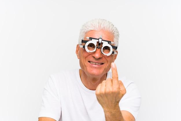 Starszy kaukaski mężczyzna ubrany w ramkę próbną okulisty, wskazując palcem na ciebie, jakby zapraszając podejść bliżej.