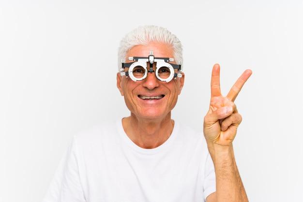 Starszy kaukaski mężczyzna ubrany w ramkę próby optyka pokazano numer dwa z palcami.