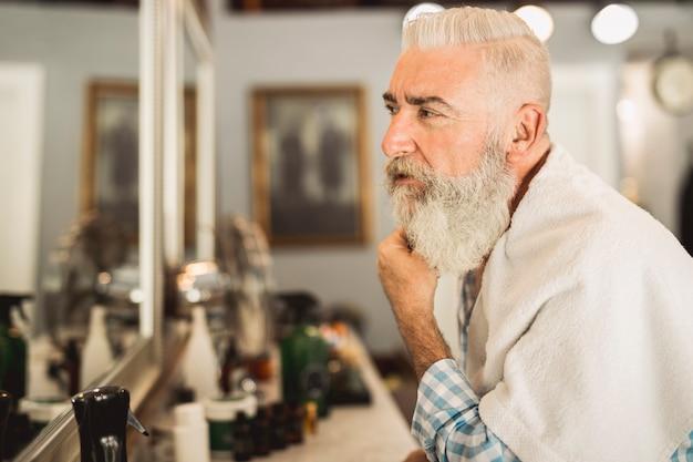 Starszy klient oceniający pracę fryzjera w zakładzie fryzjerskim