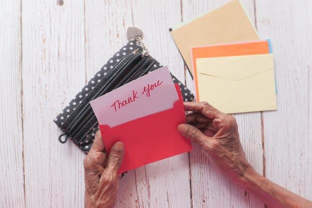 Starszy kobiet ręka trzyma notatkę z podziękowaniami, z góry na dół.