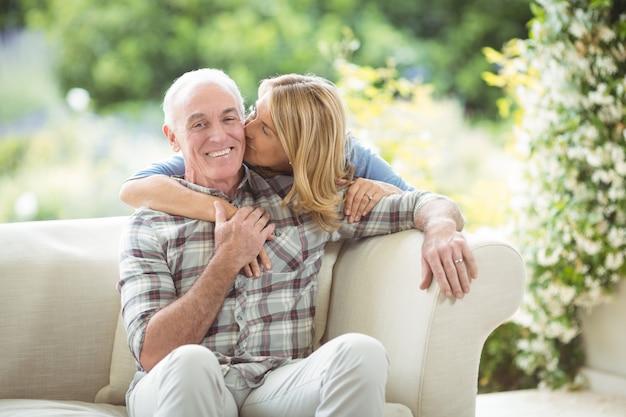 Starszy kobieta całuje mężczyznę w policzek w salonie