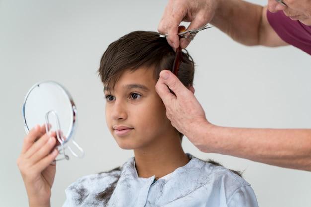 Starszy kobieta cięcia włosów chłopca