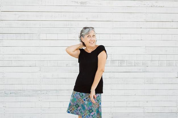 Starszy kobieta co grymas na białej powierzchni