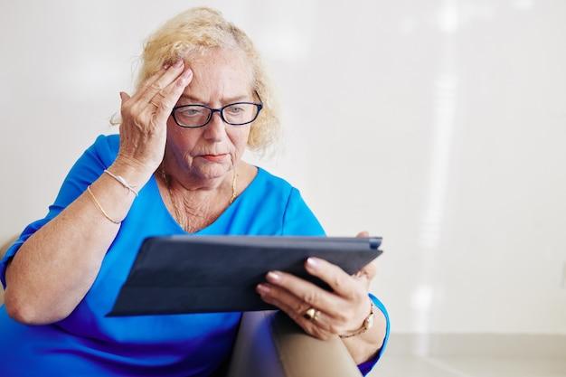 Starszy kobieta czytająca niepokojące wiadomości
