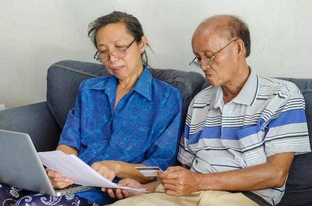 Starszy kobieta i mężczyzna szuka dokumentów biznesowych komputera i karty kredytowej