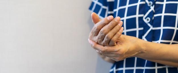 Starszy kobieta masaż pod ręką, aby złagodzić ból podczas ciężkiej pracy