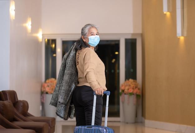 Starszy kobieta nosi maskę ochronną przeciągnij bagaż.