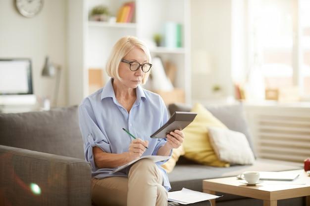 Starszy kobieta obliczania budżetu