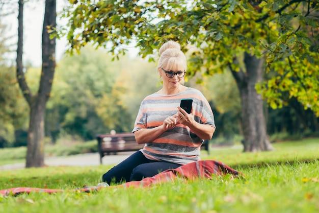 Starszy kobieta odpoczywa w parku siedzi na trawie, przy użyciu telefonu i laptopa i czyta książkę