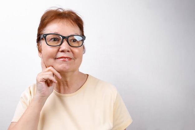 Starszy kobieta odwraca wzrok w okularach na białym tle w lekkiej koszulce.