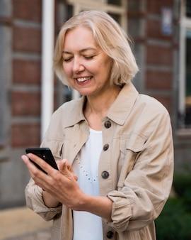 Starszy kobieta patrząc na smartfona w mieście