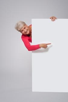 Starszy kobieta pokazuje na pustej tablicy