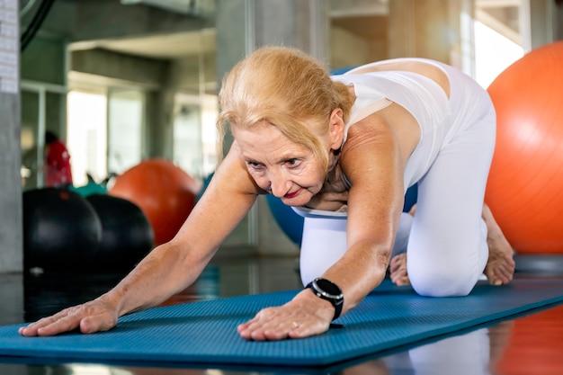Starszy kobieta rasy kaukaskiej robi ćwiczenia jogi w siłowni fitness.