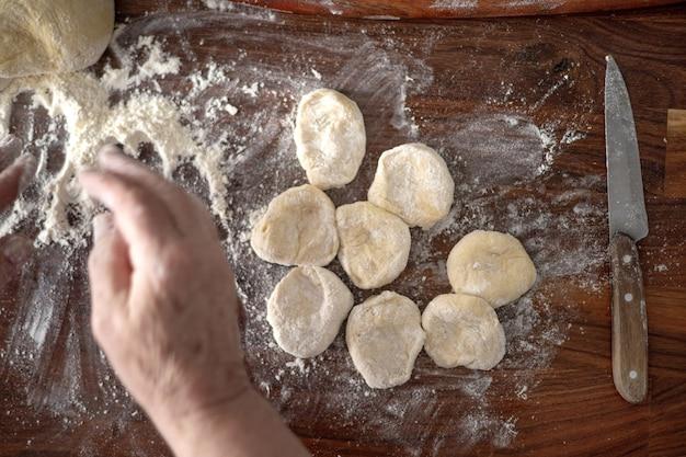 Starszy kobieta ręce toczenia ciasta w mące z wałkiem do ciasta w jej domowej kuchni