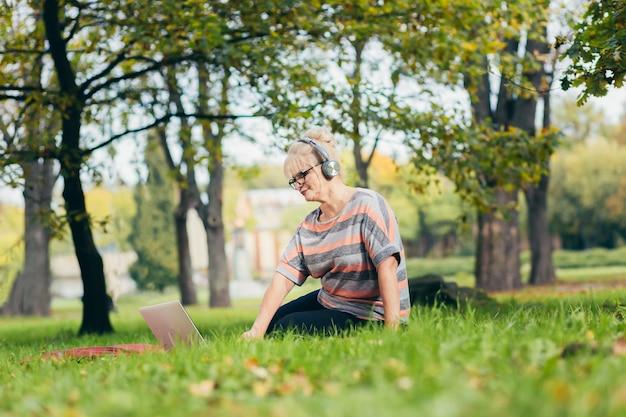 Starszy kobieta relaks w parku z laptopem