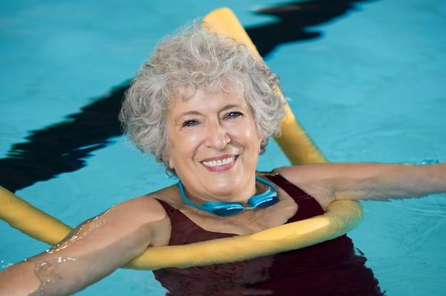 Starszy kobieta robi fitness aqua z makaronem pływać