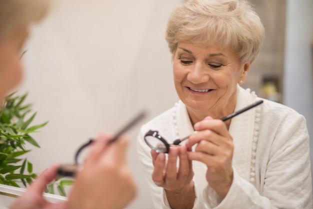 Starszy kobieta robi jej makijaż