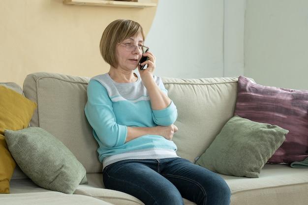Starszy kobieta rozmawia przez telefon komórkowy, siedząc na kanapie
